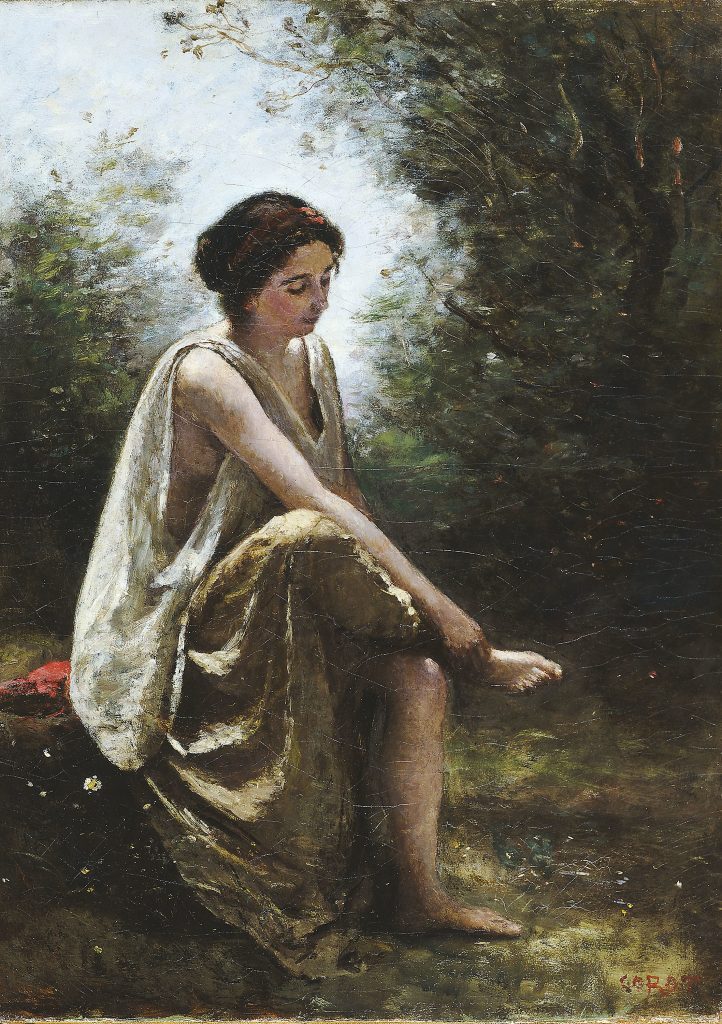 Young Grecian woman in a forest setting sitting on a log inspecting a wound in her foot